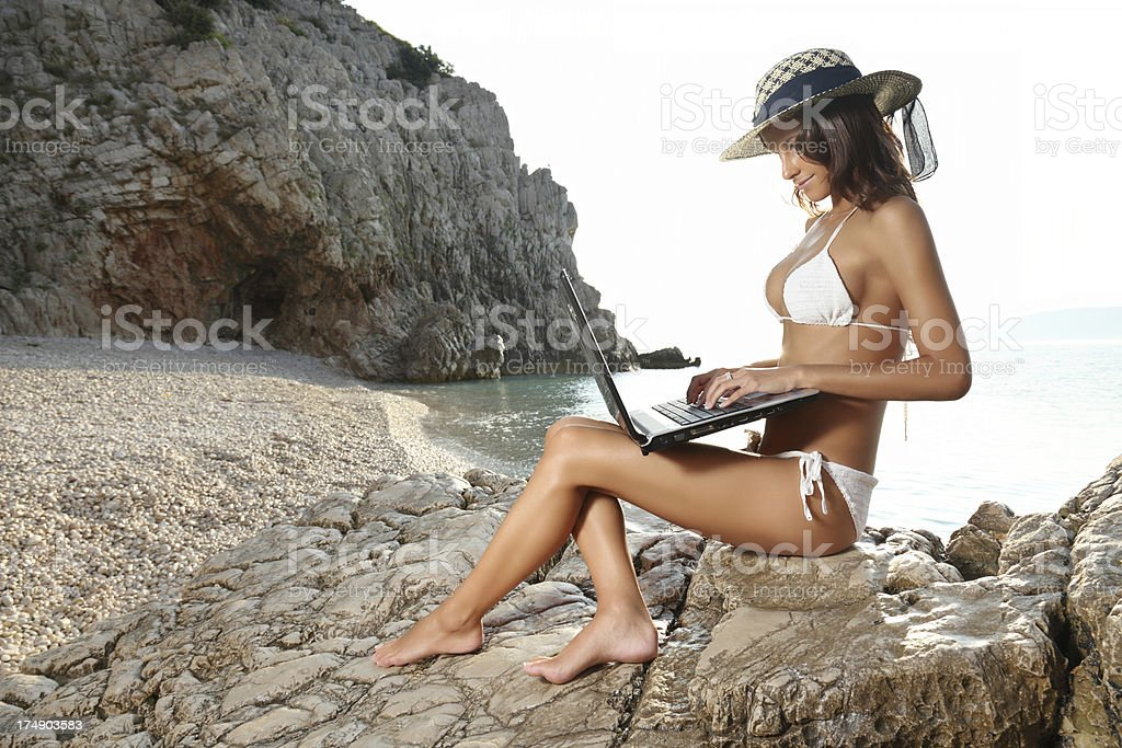 Young woman with laptop on the beach royalty-free stock photo