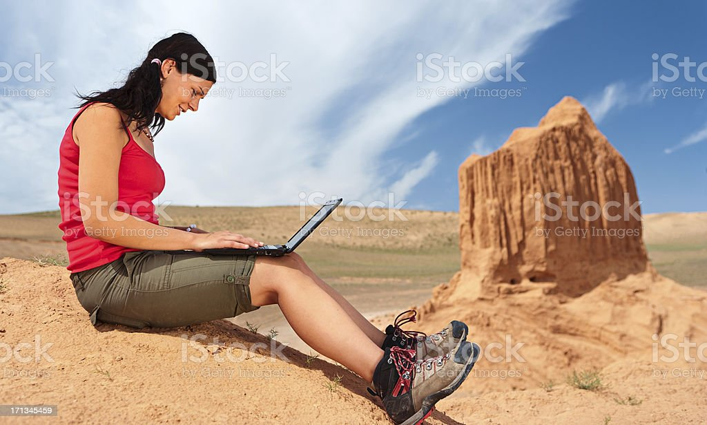 Young woman with laptop on the red cliff royalty-free stock photo