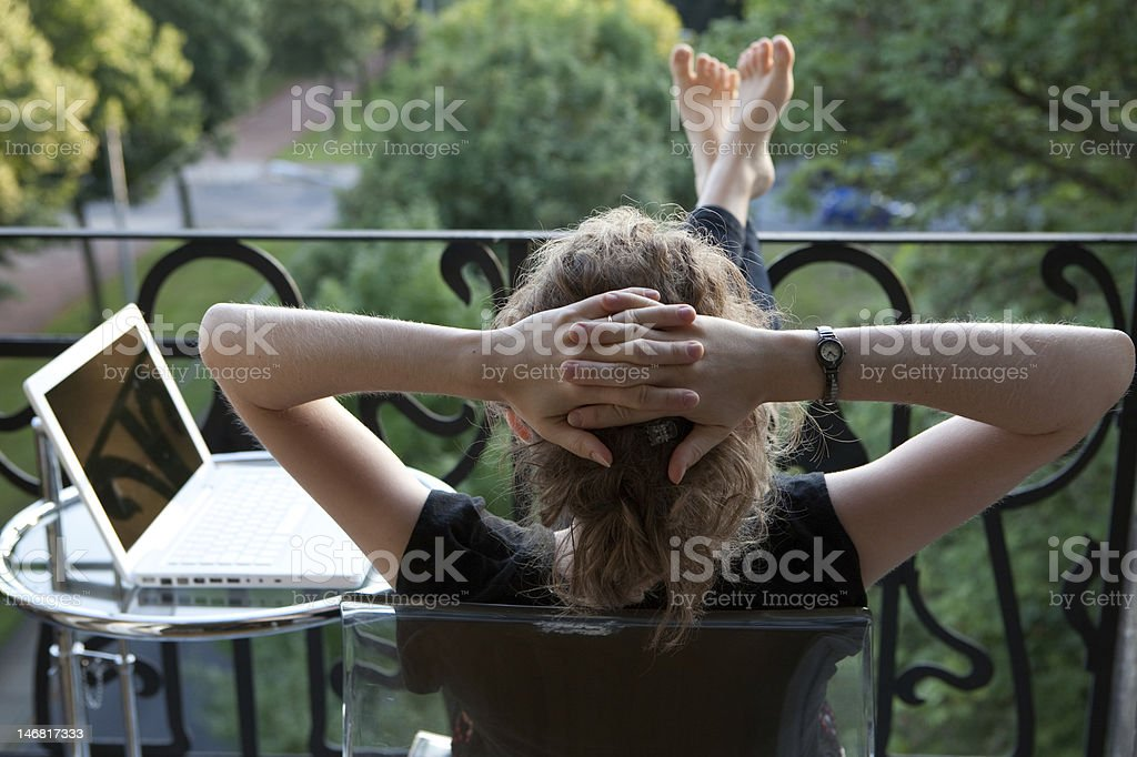 Young woman with laptop relaxing on balcony stock photo
