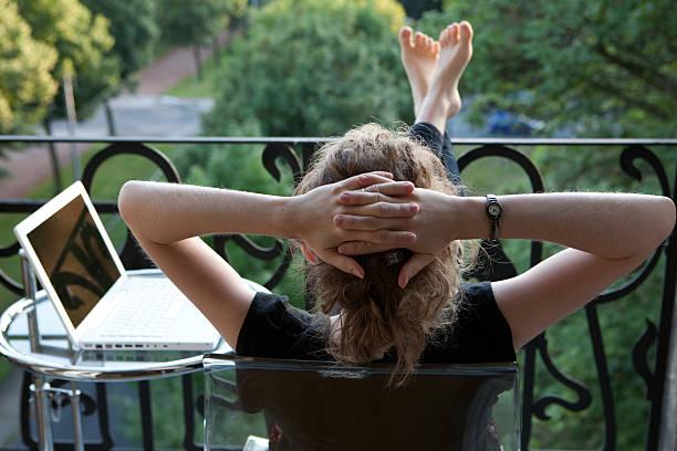 junge frau mit laptop entspannen auf balkon - garden types stock-fotos und bilder