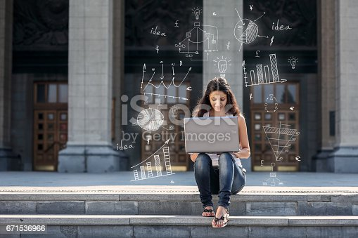 istock Young woman with laptop sitting on the stairs, near university 671536966