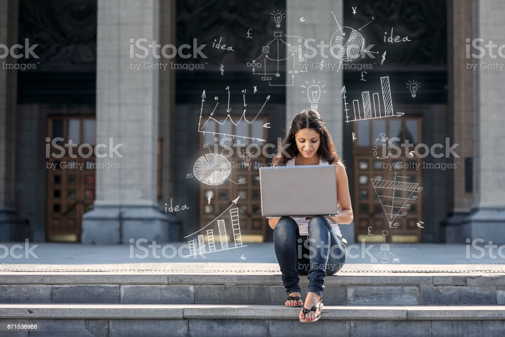 Young woman with laptop sitting on the stairs, near university stock photo