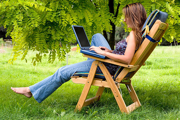 Young woman with laptop sitting outdoors on wooden deck chair stock photo