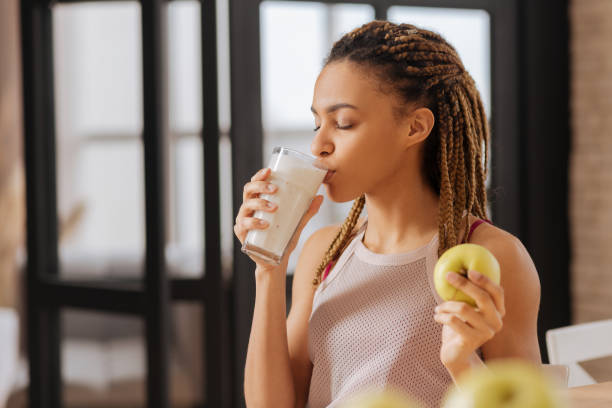 Young woman with little braids drinking glass of milk Glass of milk. Young woman with little braids drinking glass of milk in the morning at home one young woman only stock pictures, royalty-free photos & images