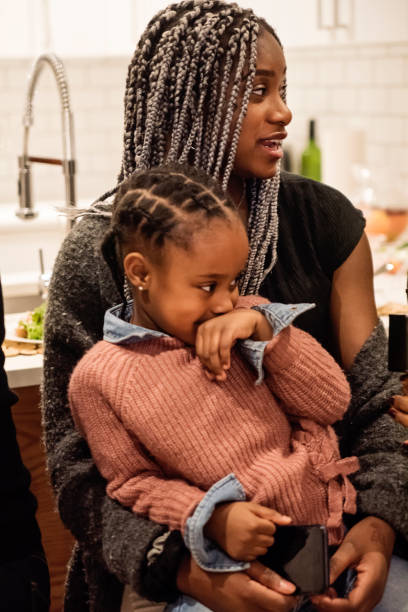 Young woman with little girl at Thanksgiving dinner. Family time for Thanksgiving dinner. Multi-generation members of african-american having fun chatting and cuddling. Cute little girl sitting on cousin's lap. Modern appartement. Vertical indoors waist up shot with some copy space. haitian ethnicity stock pictures, royalty-free photos & images