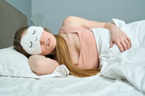Young woman with long blonde hair with sleep mask in her eyes sleeping in white bed