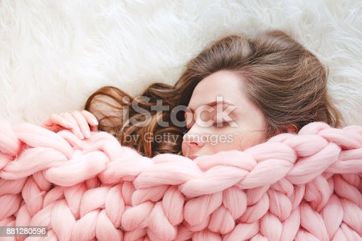istock Young woman with long brown hair sleeping under warm knitted peach color throw blanket 881280596