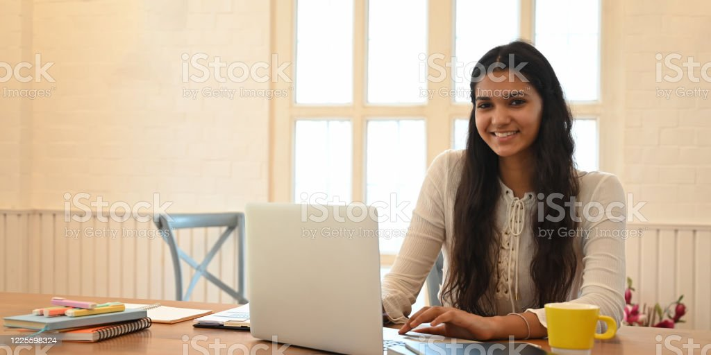 Young woman with long curly hair smiling and typing on computer laptop while sitting at the wooden working desk over comfortable sitting room windows as background. Young woman with long curly hair smiling and typing on computer laptop while sitting at the wooden working desk over comfortable sitting room windows as background. Adult Stock Photo
