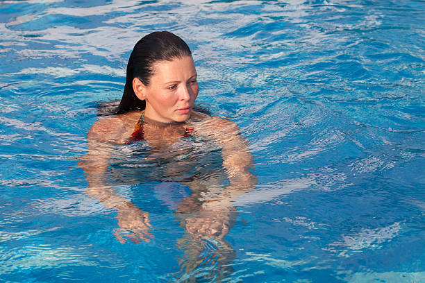 Young woman with long dark hair in a swimming pool stock photo