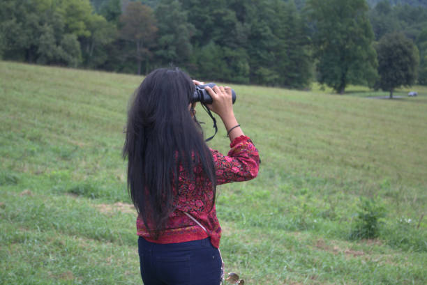 YOung woman with long, dark hair looking out over a field with binoculars stock photo