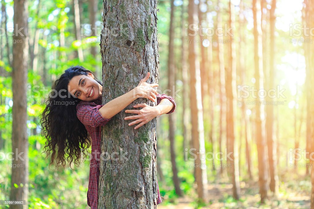 Young woman with long hair embracing tree in the forest – Foto
