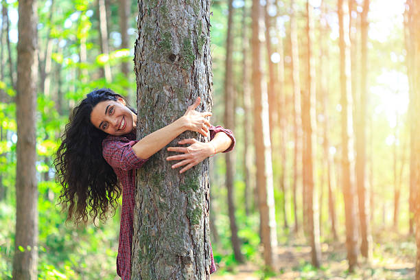 Young woman with long hair embracing tree in the forest Playful young woman embracing a tree in the forest. Standing and looking at camera. Trees and sunbeam on background. tree hugging stock pictures, royalty-free photos & images