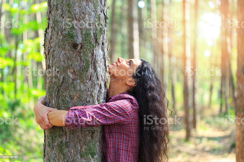 Young woman with long hair hugging tree in the forest – Foto