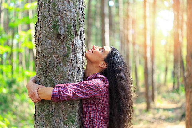 Young woman with long hair hugging tree in the forest Cheerful young woman embracing a tree in the forest. Standing and looking up. Trees and sunbeam on background. tree hugging stock pictures, royalty-free photos & images