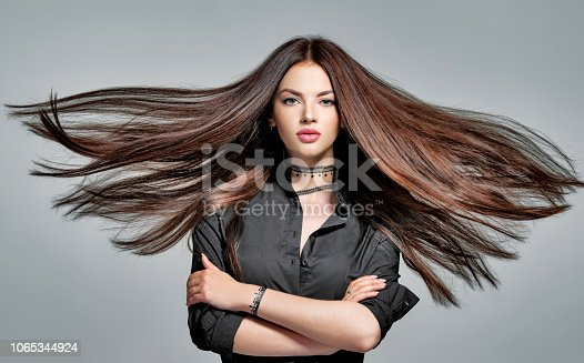 Young woman with long straight hair - at studio. Portrait of an attractive brunette girl. Fashion model wears black shirt anf jeans. beautiful female model