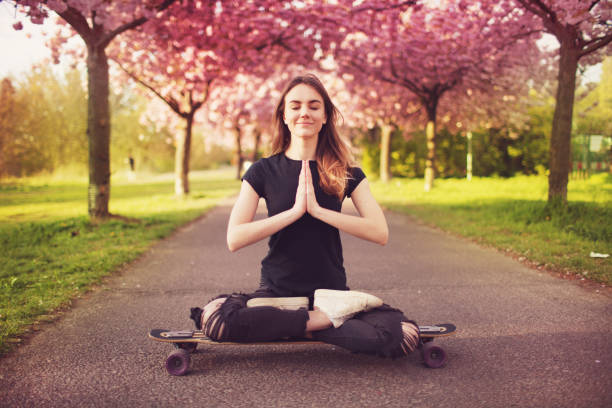 Young woman with longboard in cherry blossom alley stock photo