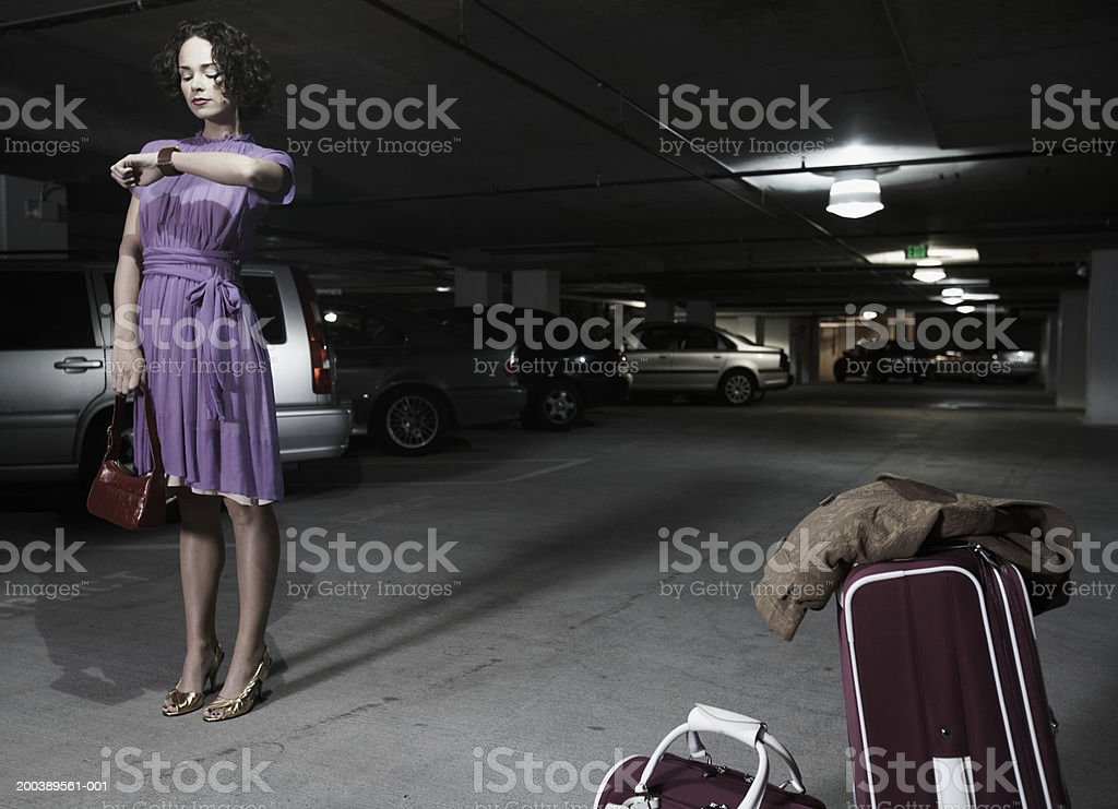 Young woman with luggage looking at watch in parking garage stock photo