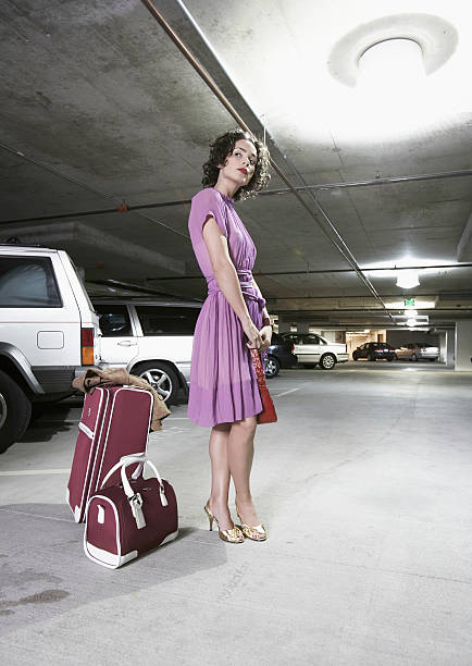 Young woman with luggage standing in parking garage, side view stock photo