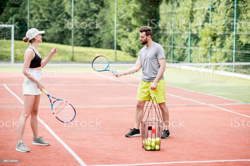 Young woman with male insructor playing tennis royalty-free stock photo
