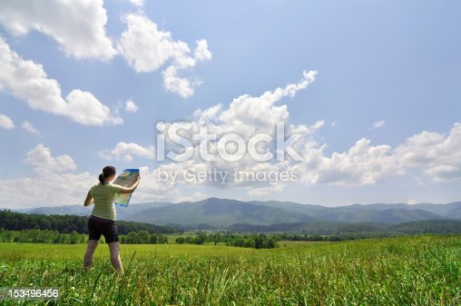 483422527istockphoto young woman with map exploring a vast wilderness 153496456