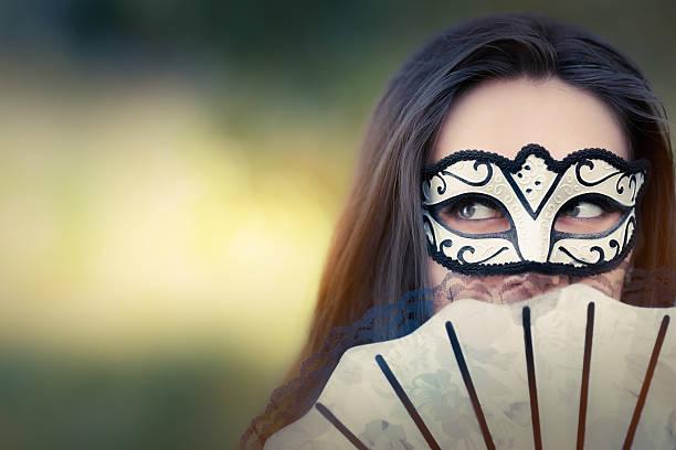 junge frau mit maske und ventilator - geheime garten parties stock-fotos und bilder