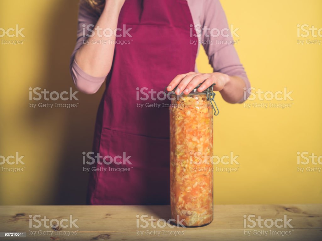 Young woman with massive jar of kimchi stock photo