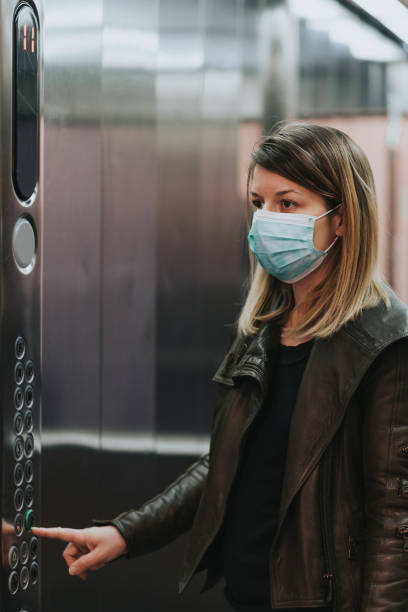Young woman with medical mask in the elevator of an apartment building stock photo