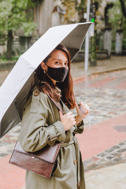young woman with medical mask outdoors walking by street under rain stock photo