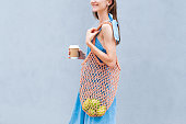 istock Young woman with mesh reused shopping bag holding a take-off cup of coffee 1172438239