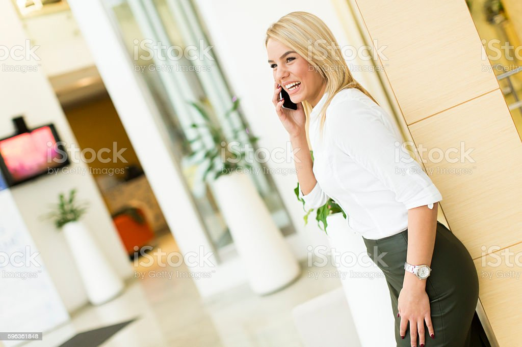 Young woman with mobile phone in the office royalty-free stock photo