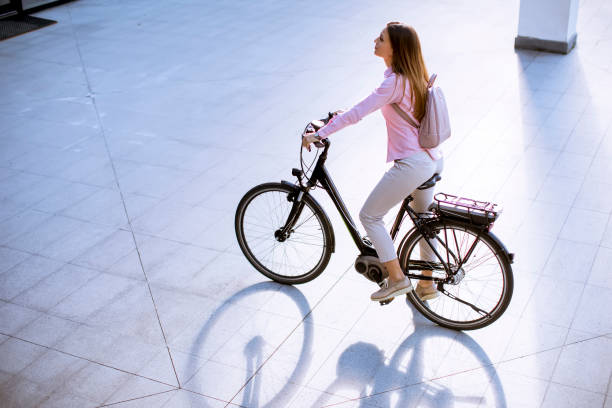 Young woman with modern city electric e-bike clean sustainable urban transportation stock photo