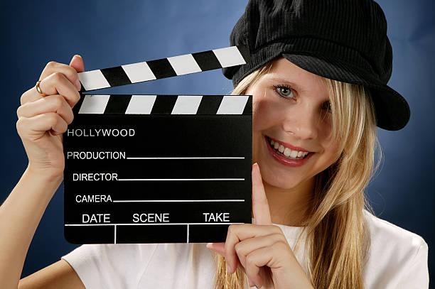 junge frau mit film action schindel - klappe hut stock-fotos und bilder