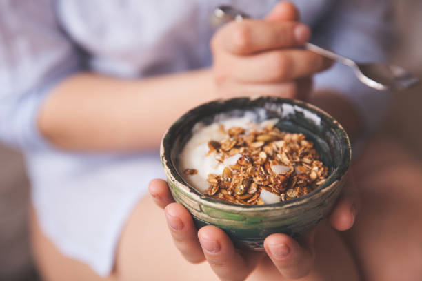 young woman with muesli bowl. girl eating breakfast cereals with nuts, pumpkin seeds, oats and yogurt in bowl. girl holding homemade granola. healthy snack or breakfst in the morning. - oats food stock photos and pictures