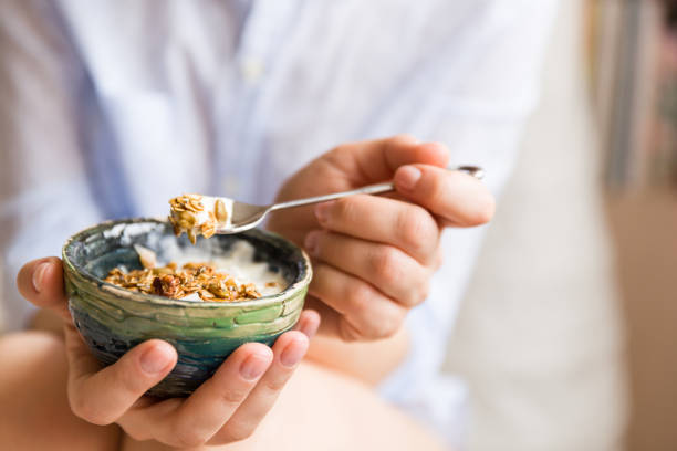 Young woman with muesli bowl. Girl eating breakfast cereals with nuts, pumpkin seeds, oats and yogurt in bowl. Girl holding homemade granola. Healthy snack or breakfast in the morning. stock photo