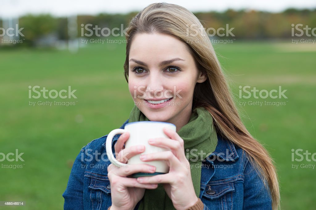 young woman with mug outdoors stock photo