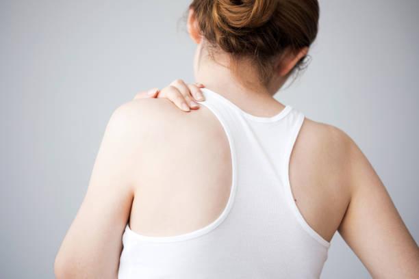junge frau mit nackenschmerzen - schultersteife stock-fotos und bilder