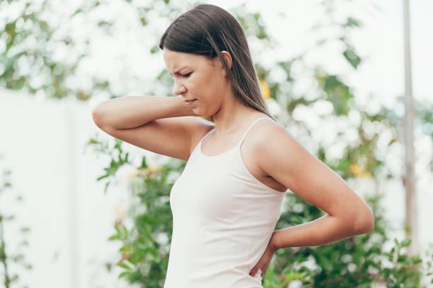 junge frau mit nackenschmerzen im freien - hals übungen stock-fotos und bilder
