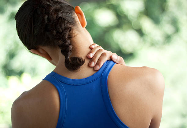 Young woman with neck pain Young woman in sportswear with neck pain. You may also like: cervical vertebrae stock pictures, royalty-free photos & images