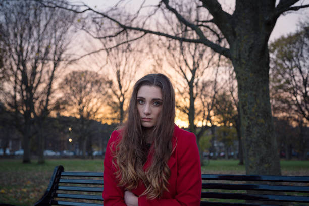 Young woman with negative thoughts and unhappy sitting alone on a park bench stock photo