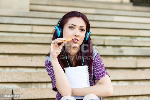 istock young woman with note pad sitting at stairs 616001922
