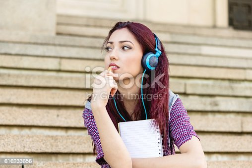 istock young woman with note pad sitting at stairs 616233656