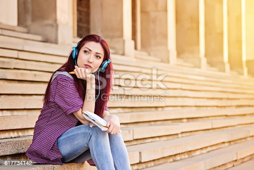 istock young woman with note pad sitting at stairs 617734142