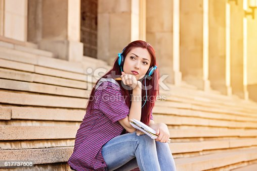 istock young woman with note pad sitting at stairs 617737508