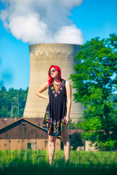 Young Woman With Nuclear Power Plant Behind Her A beautiful 19 year old female standing in front of a nuclear power plant. sdominick stock pictures, royalty-free photos & images