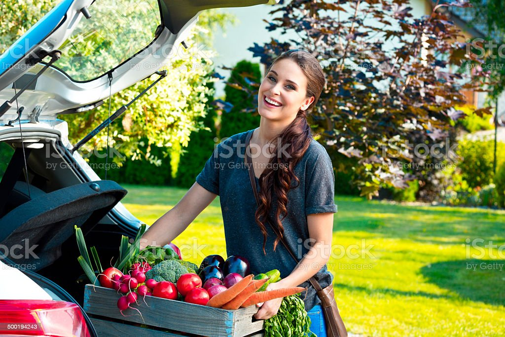 Young woman with organic food Young woman taking out the car trunk a box with organic food, smiling at the camera. Adult Stock Photo