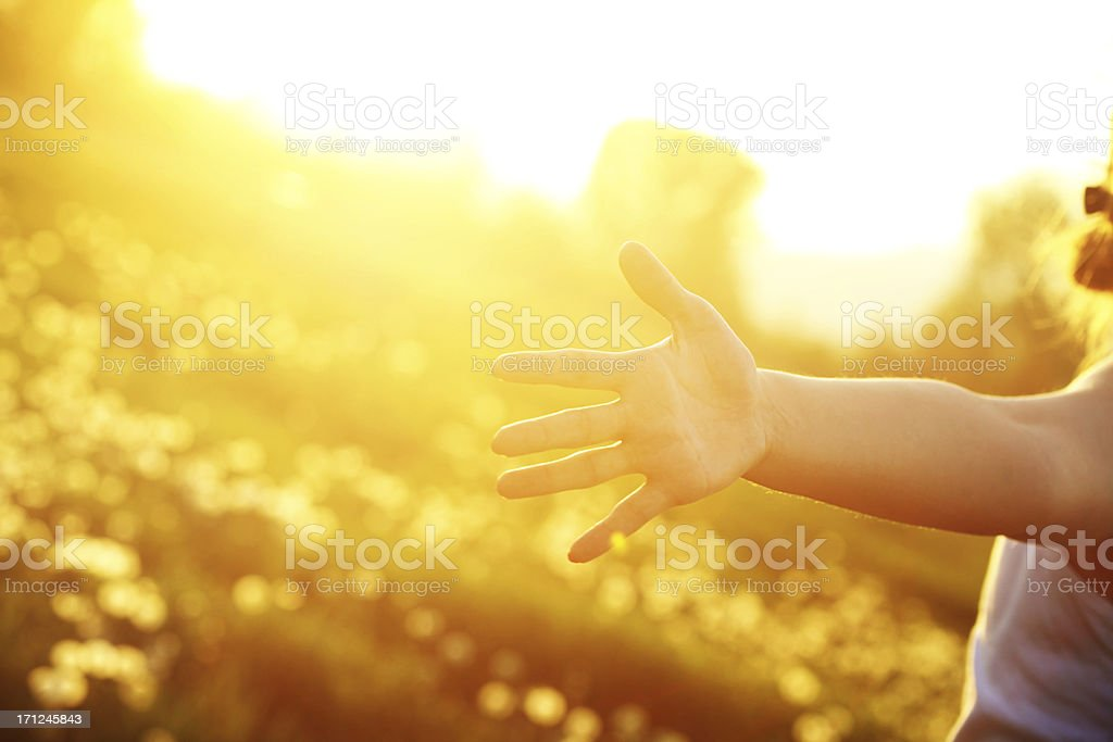 Young woman with outstretched arms in the sunlight royalty-free stock photo