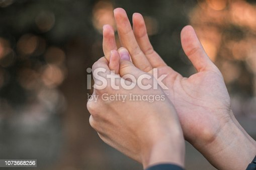 Young woman with pain on finger, bokeh background