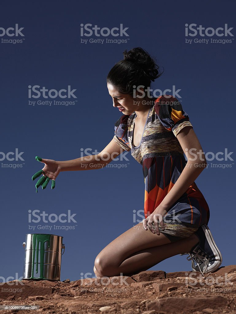 Young woman with paint on fingers, side view royalty-free stock photo