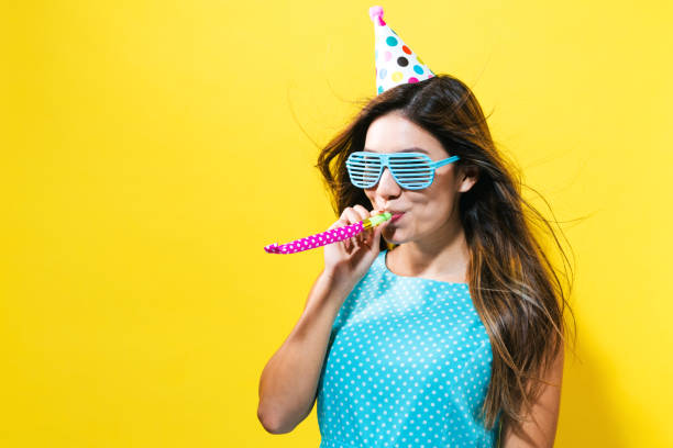 young woman with party hat with noisemaker - girls party zdjęcia i obrazy z banku zdjęć