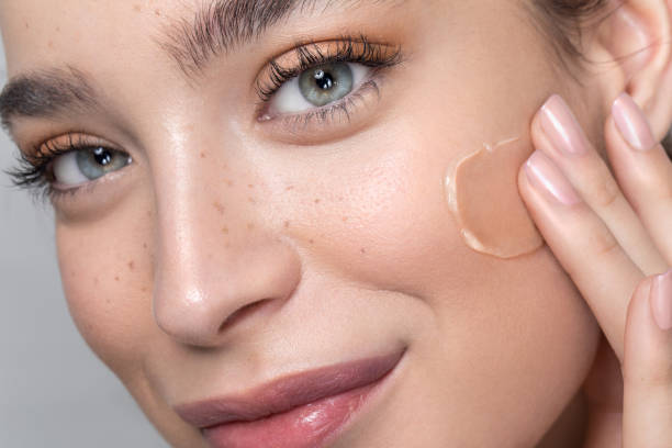 Young woman with perfect skin applying foundation stock photo